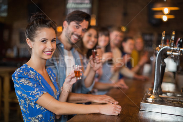 Happy young friends holding short glasses at counter Stock photo © wavebreak_media