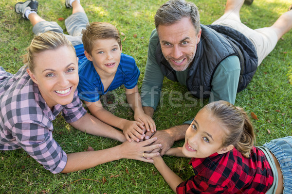 Happy family lying and putting their hands together in park Stock photo © wavebreak_media