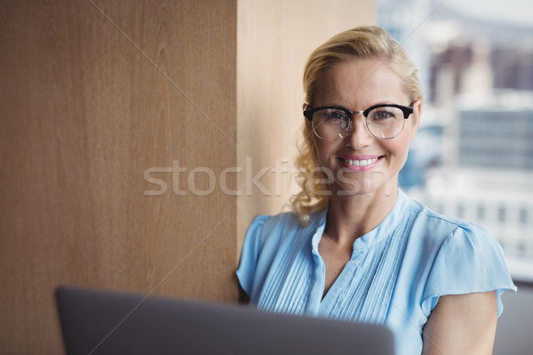 Portrait souriant exécutif utilisant un ordinateur portable bureau femme Photo stock © wavebreak_media