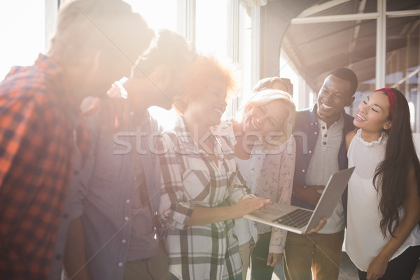 Happy businesswoman holding laptop while standing with colleagues Stock photo © wavebreak_media