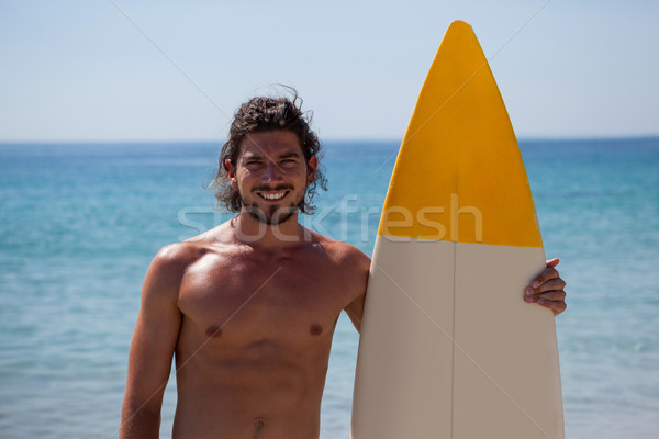 Smiling surfer with surfboard standing at beach coast Stock photo © wavebreak_media