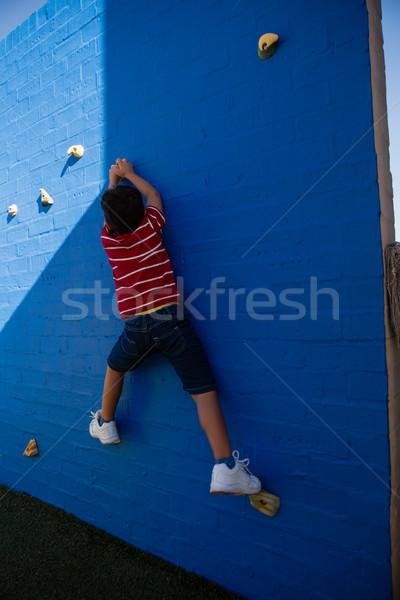 Rear view of boy climbing blue wall at playground Stock photo © wavebreak_media