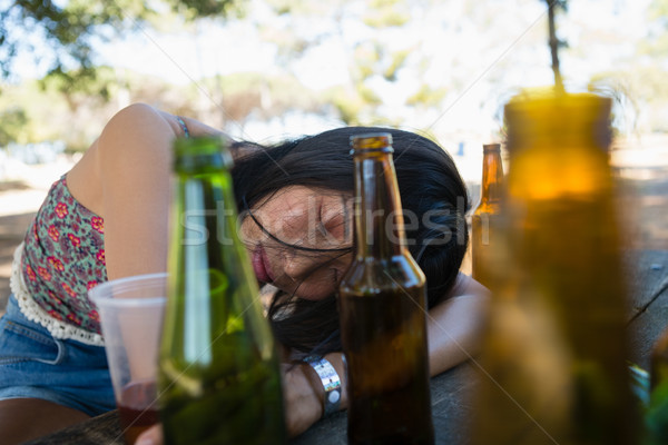 Drunken woman sleeping on the table and holding a glass of beer Stock photo © wavebreak_media