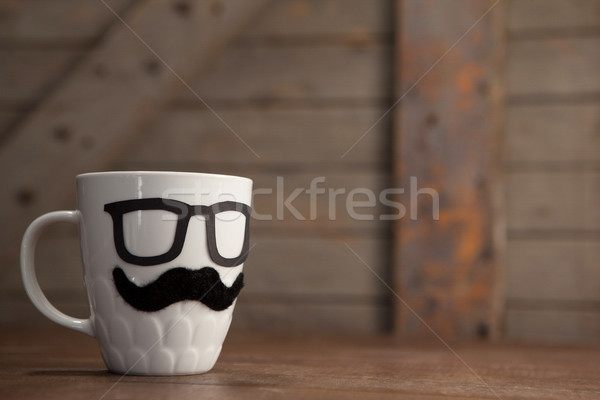 Close up of white coffee mug with mustache and eyeglasses on table Stock photo © wavebreak_media