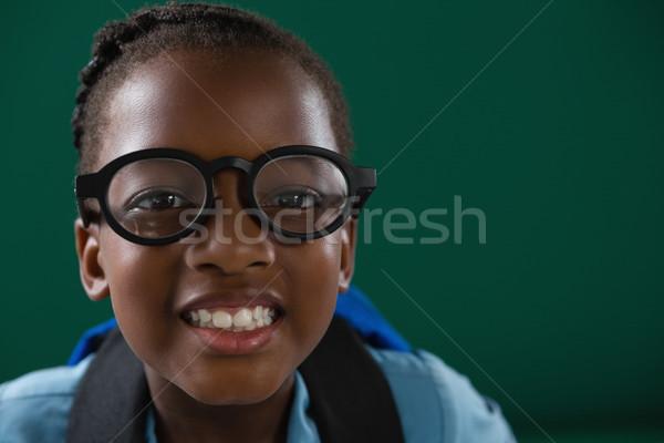 Souriant écolière permanent vert portrait Photo stock © wavebreak_media