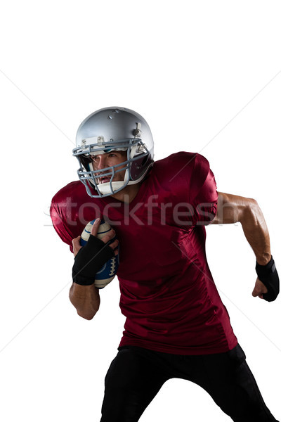 Focused football player wearing helmet holding ball while playing Stock photo © wavebreak_media