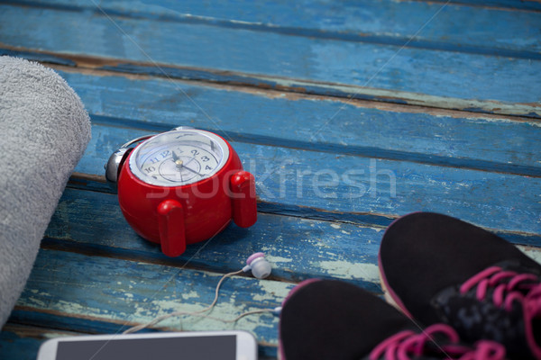 High angle view of alarm clock by mobile phone amidst napkin and sports shoes Stock photo © wavebreak_media