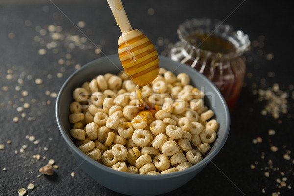 Honey being poured in bowl of cereal rings Stock photo © wavebreak_media
