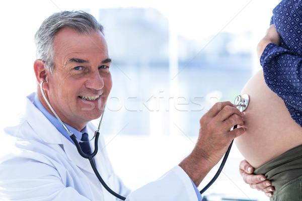 Portrait of male doctor examining pregnant woman in clinic Stock photo © wavebreak_media