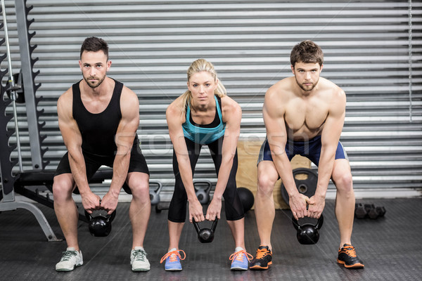 Stock photo: Fit people lifting dumbbells