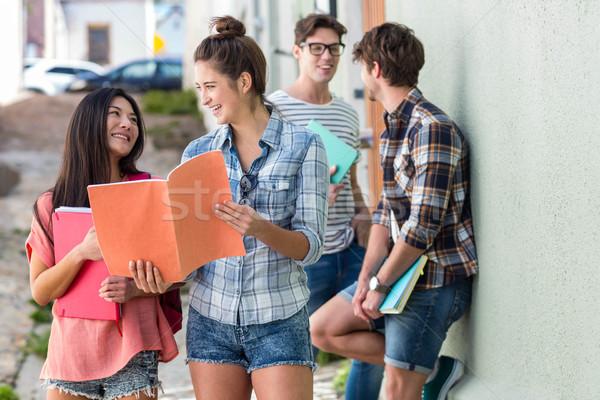 Hip friends reading notes on notebook Stock photo © wavebreak_media