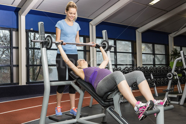 Smiling trainer helping pregnant woman lifting barbell Stock photo © wavebreak_media