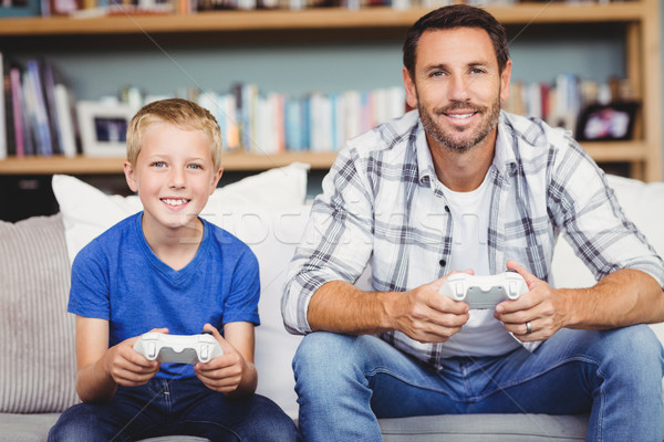 Portrait of smiling father and son playing video game Stock photo © wavebreak_media