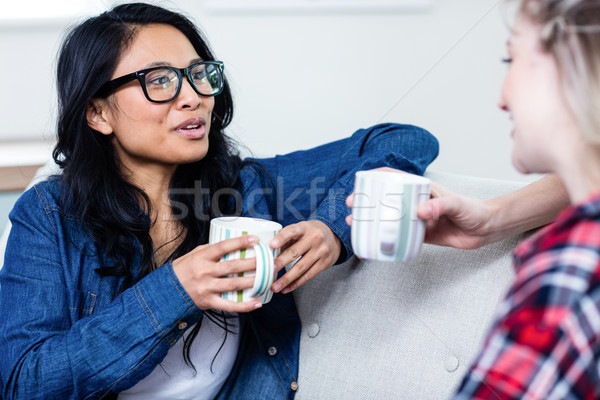 Young woman talking with female friend while drinking coffee Stock photo © wavebreak_media