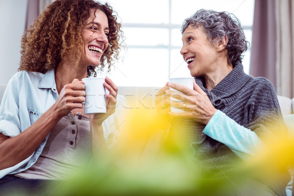 Smiling mother and daughter holding coffee mugs while discussing Stock photo © wavebreak_media