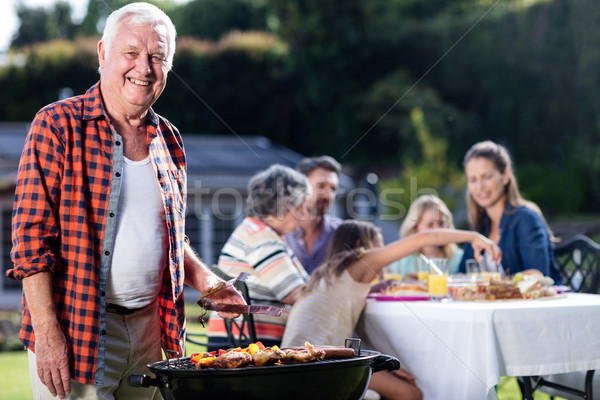 Stock photo: Senior man at barbecue grill while family having lunch in backgr