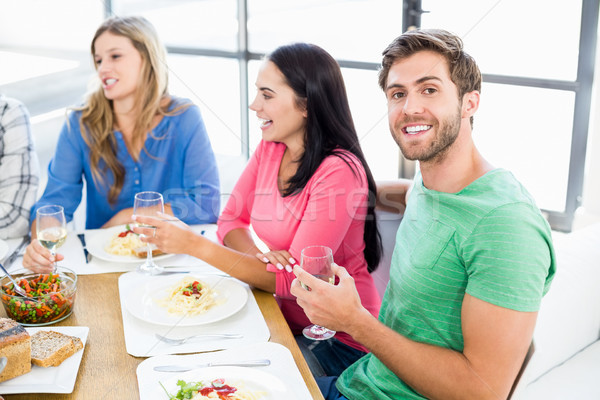 Man sitting with friends at dinning table Stock photo © wavebreak_media