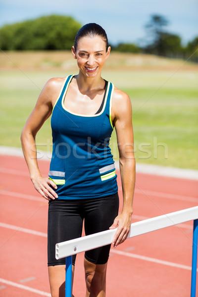 Portrait of female athlete standing beside hurdle Stock photo © wavebreak_media