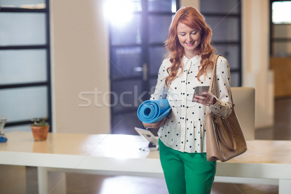 Smiling woman using phone while holding mat in office Stock photo © wavebreak_media