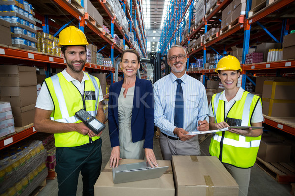 Warehouse manager and client standing with co-workers Stock photo © wavebreak_media