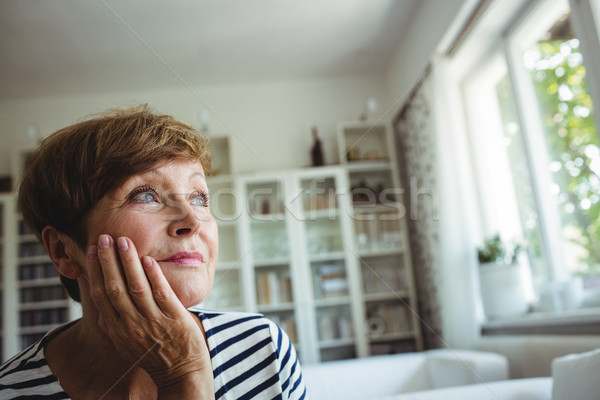 Thoughtful senior woman sitting on sofa in living room Stock photo © wavebreak_media