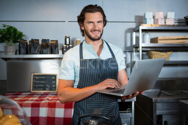 Smiling male staff using laptop at counter Stock photo © wavebreak_media