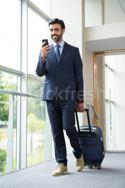 Businessman with trolley bag using mobile phone Stock photo © wavebreak_media