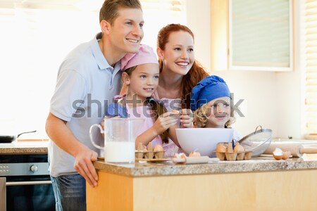Happy family eating biscuits and drinking milk Stock photo © wavebreak_media