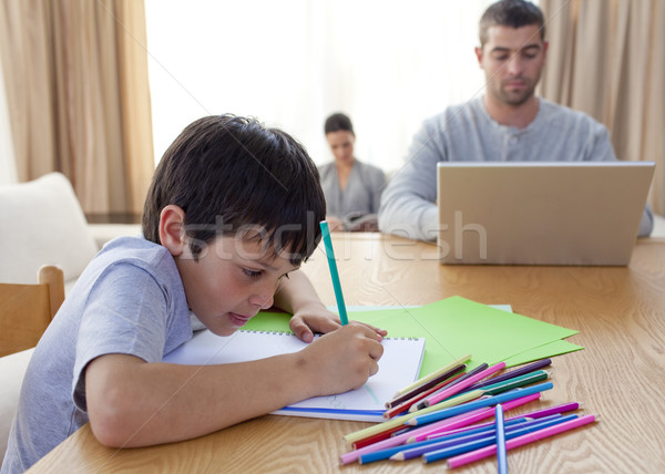 Boy painting and parents working at home Stock photo © wavebreak_media