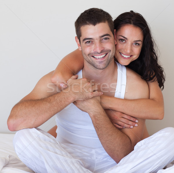 Happy lovers embracing lying in bed Stock photo © wavebreak_media