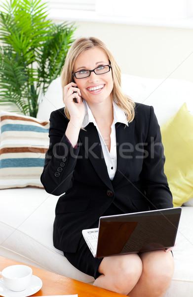 Ambitieux parler téléphone utilisant un ordinateur portable séance canapé Photo stock © wavebreak_media