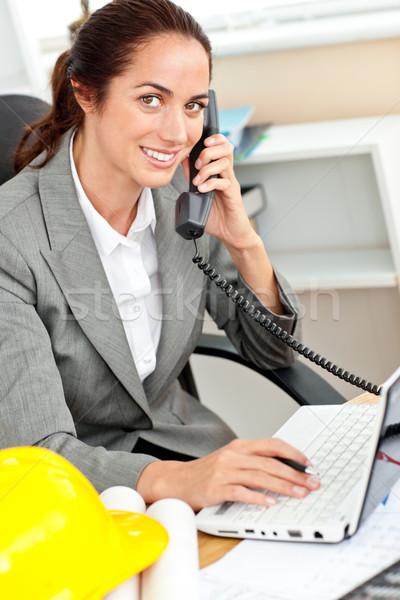 Smiling female architect talking on phone and using her laptop in her office at her desk Stock photo © wavebreak_media