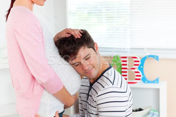 Ostrożny młody człowiek słuchania brzuch ciąży żona Zdjęcia stock © wavebreak_media
