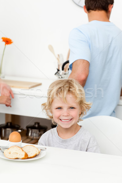 Happy boy eating boiled egg and bread in the kitchen with his father Stock photo © wavebreak_media
