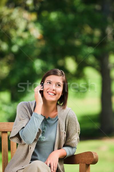 Beautiful woman phoning on the bench Stock photo © wavebreak_media