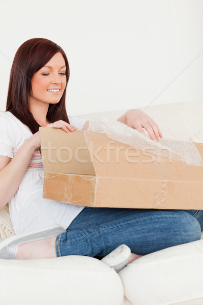 Good looking red-haired woman opening a carboard box while sitting on a sofa in the living room Stock photo © wavebreak_media