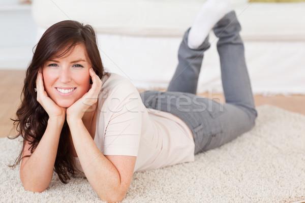 Charming brunette female posing while lying on a carpet in the living room Stock photo © wavebreak_media