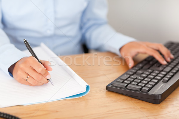 gorgeous businesswoman typing and writing in her office Stock photo © wavebreak_media