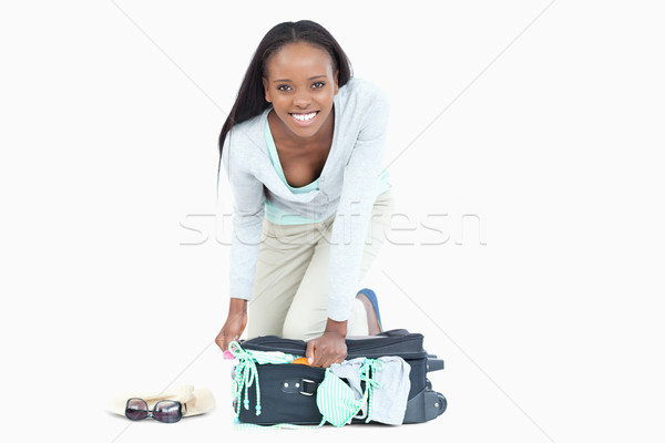 Young woman trying hard to get her suitcase closed against a white background Stock photo © wavebreak_media