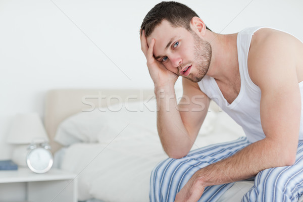Stock photo: Sick man sitting on his bed while looking at the camera