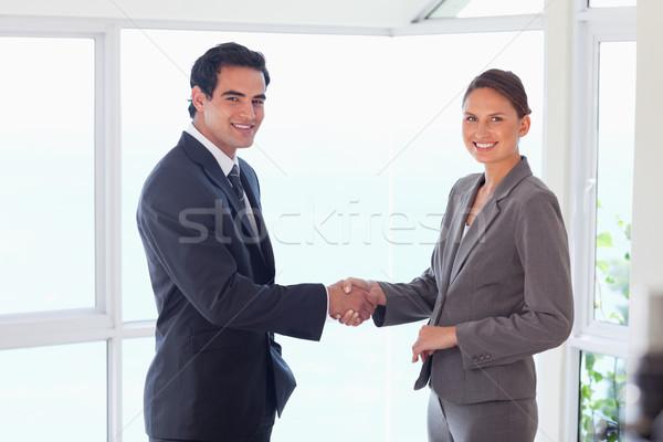 Vue de côté souriant jeunes échanges partenaire serrer la main Photo stock © wavebreak_media