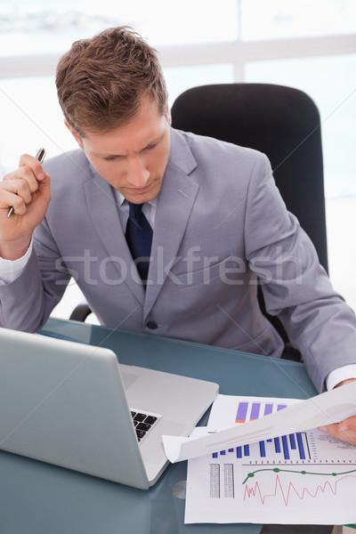 Businessman with statistics sitting at his desk Stock photo © wavebreak_media