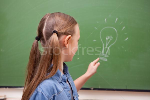 Schoolmeisje wijzend lamp Blackboard school achtergrond Stockfoto © wavebreak_media