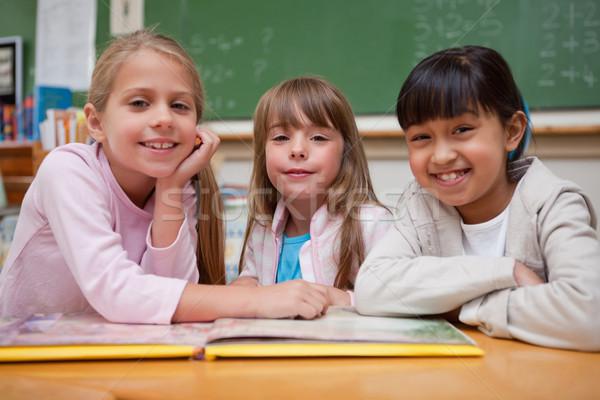 Sorridere studentesse lettura fiaba compagno di classe guardando Foto d'archivio © wavebreak_media