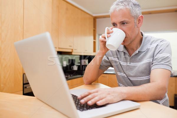 Szczęśliwy człowiek notebooka pitnej kawy kuchnia Zdjęcia stock © wavebreak_media