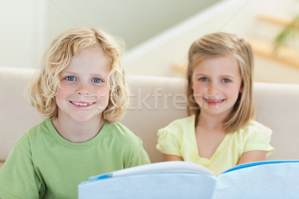 Siblings reading booklet together on the sofa Stock photo © wavebreak_media