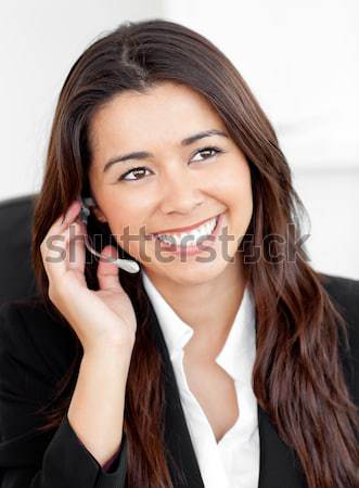 A woman lying with a quilt over her and earphones on, smiling as she looks forward. Stock photo © wavebreak_media