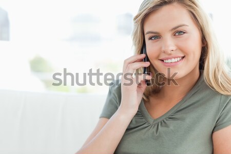 Stock photo: A woman looking in front of her smiling as she makes a call.