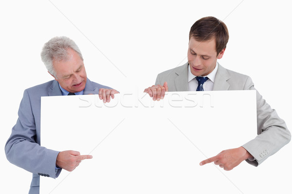 Tradesmen pointing at blank sign in their hands against a white background Stock photo © wavebreak_media