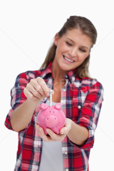 Portrait of a young woman putting a note a piggy bank against a white background Stock photo © wavebreak_media